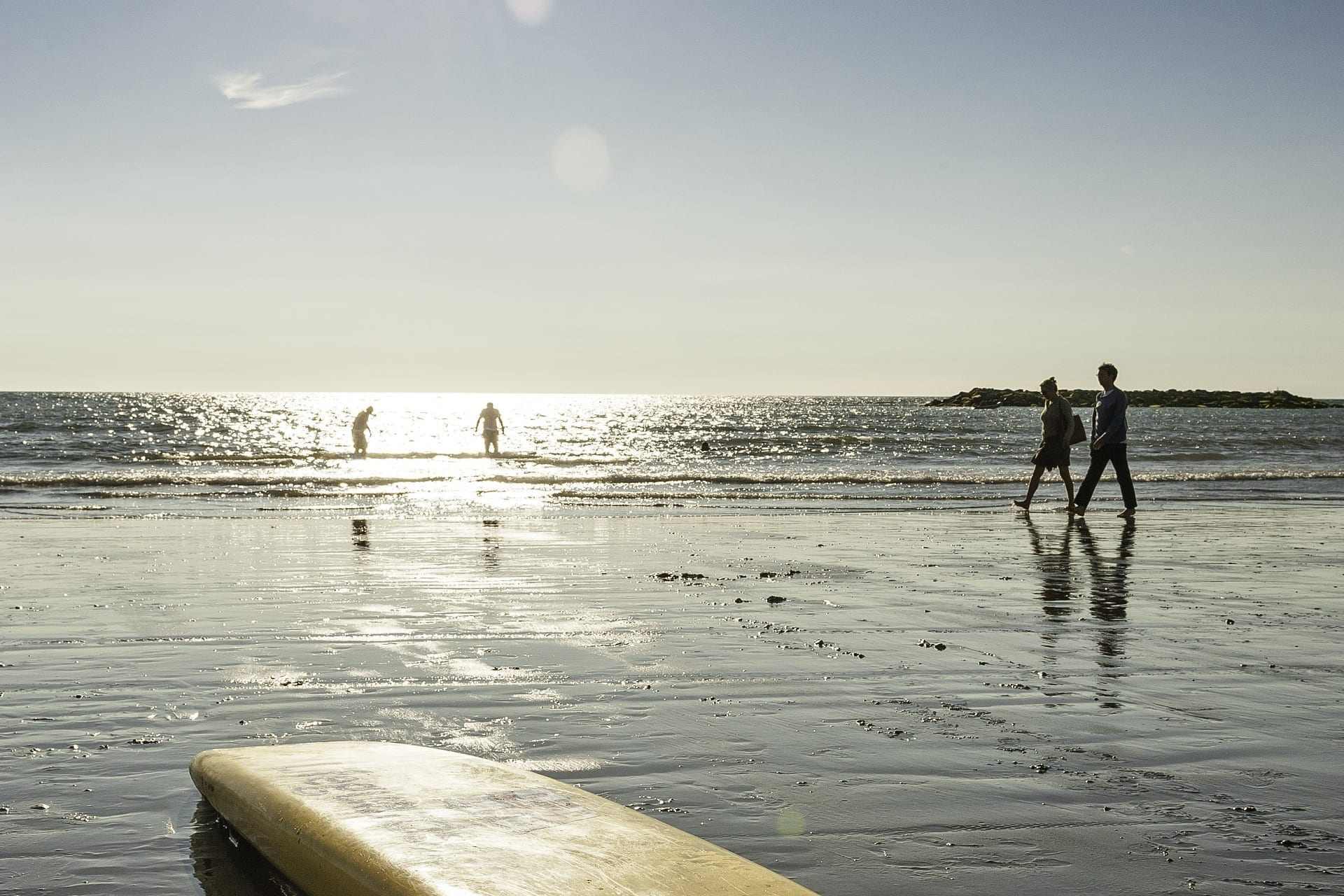 couple walking a beach in Wales near a Coastal Campsite