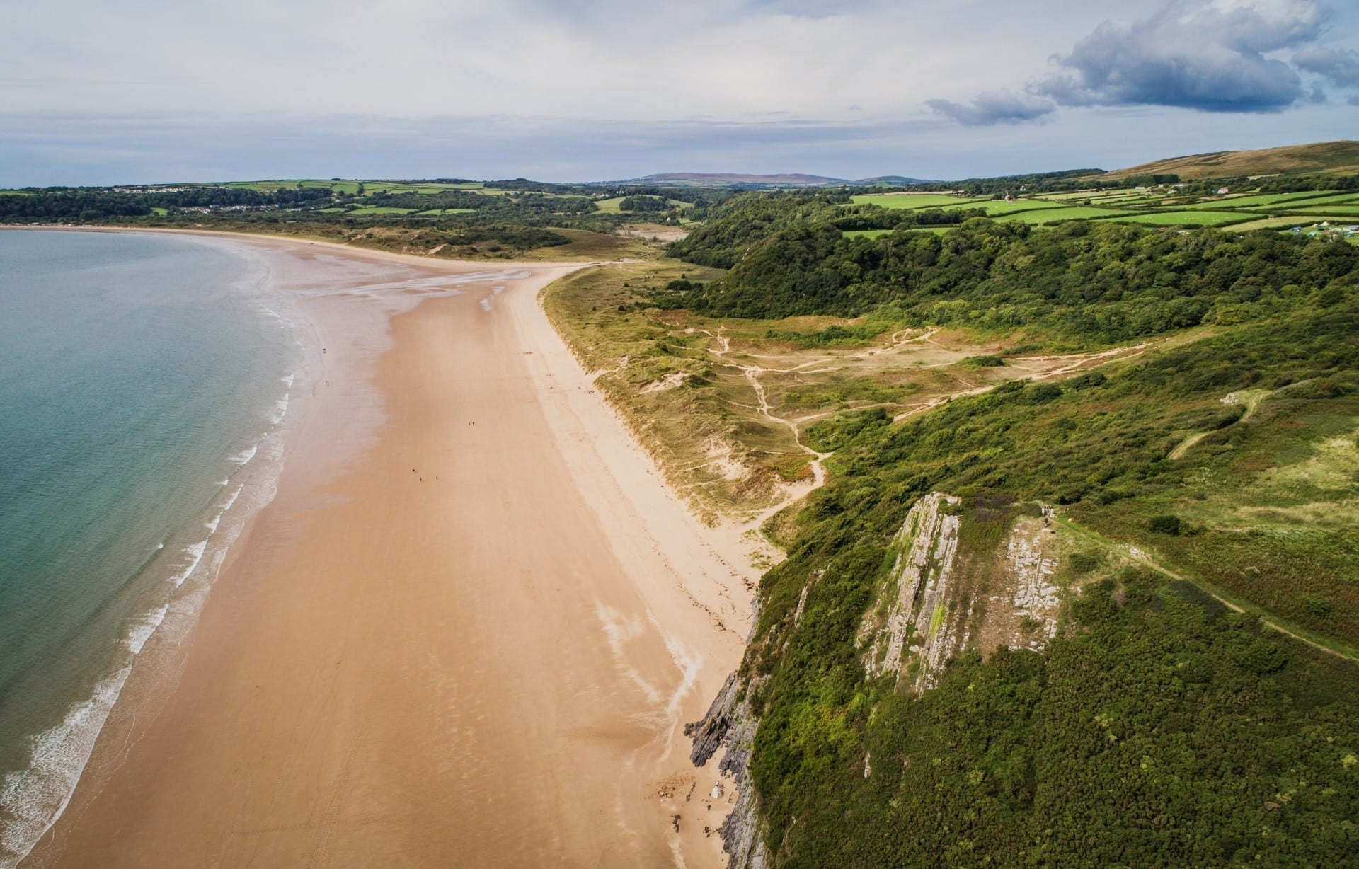 overhead view of a beach with cliffs to the right side in Wales
