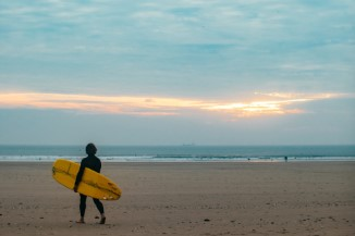 Best Surfing Beaches in Wales - A surfer with his board on a beach in Wales
