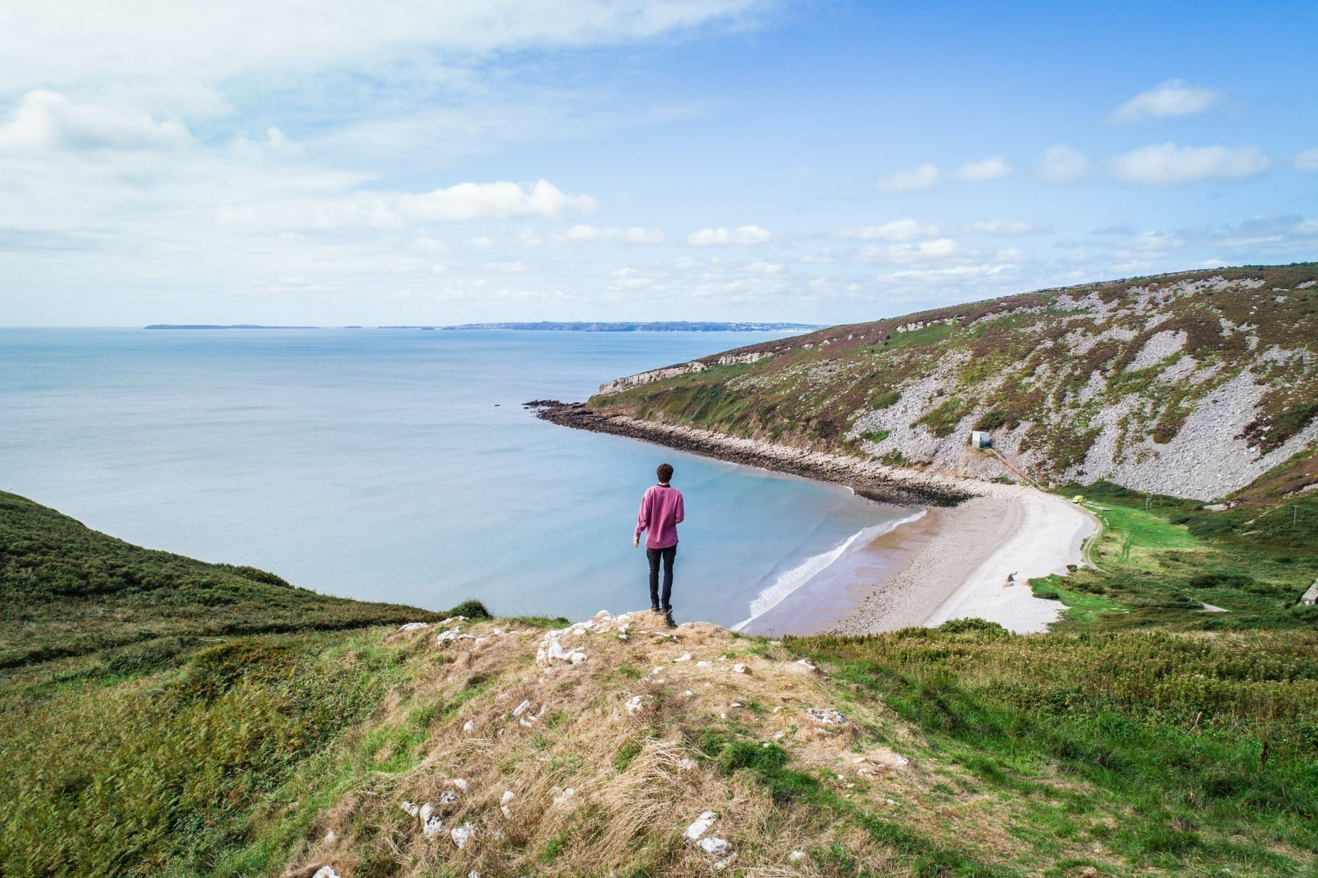 man standing on a cliff overlooking a beach cove in Wales