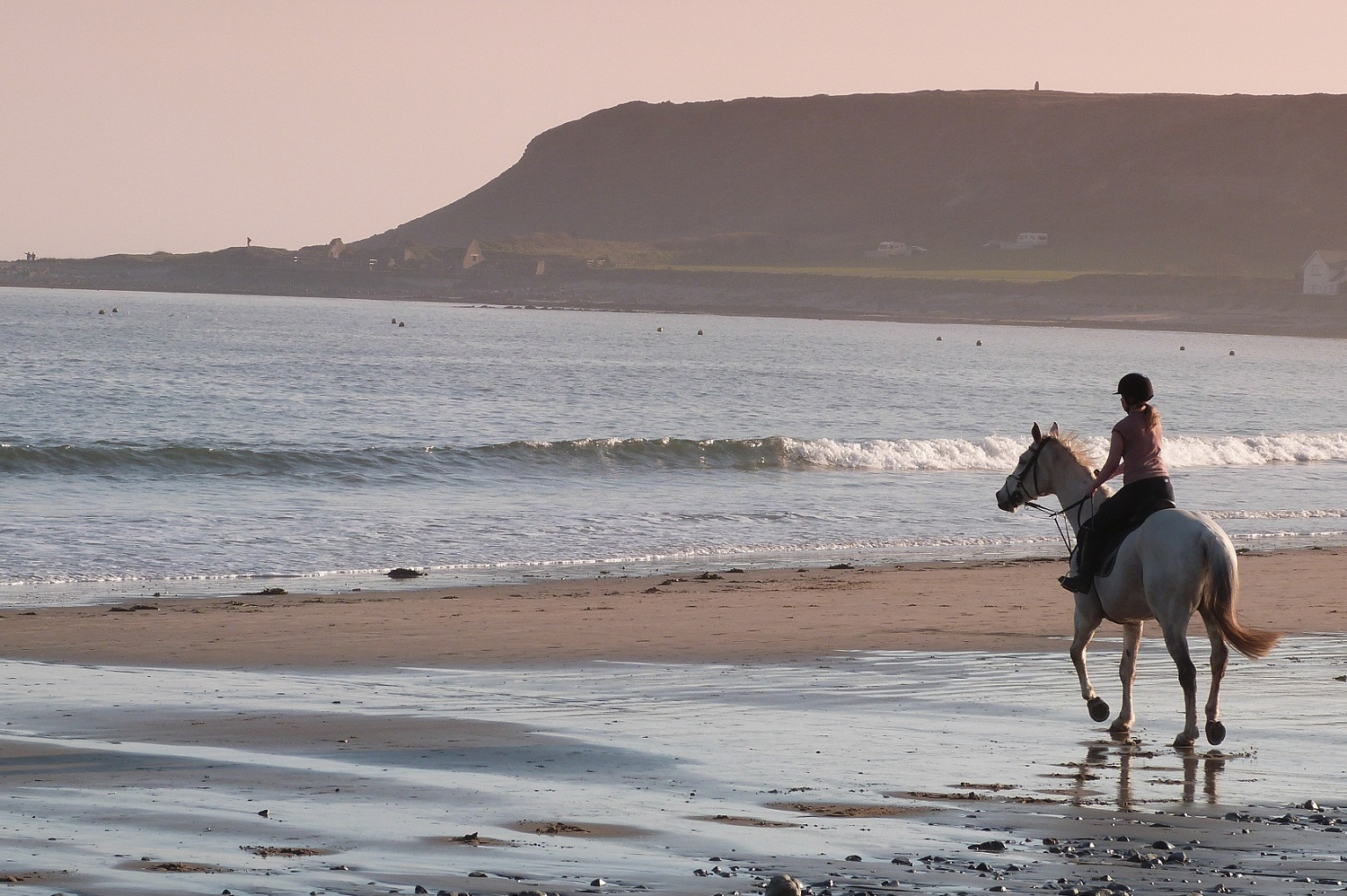 person riding a horse on a beach in wales