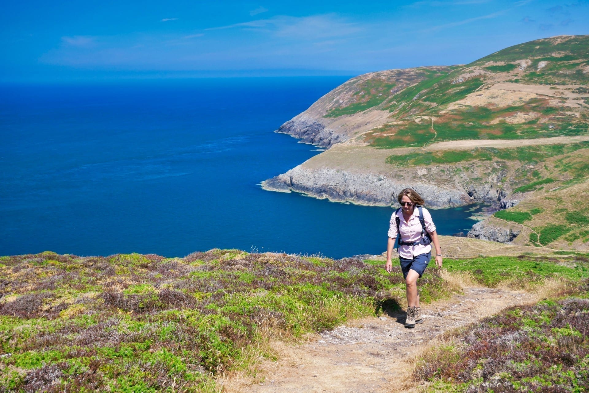 A single female walker on the Wales Coast Path on a sunny summer day with a blue sea and sky