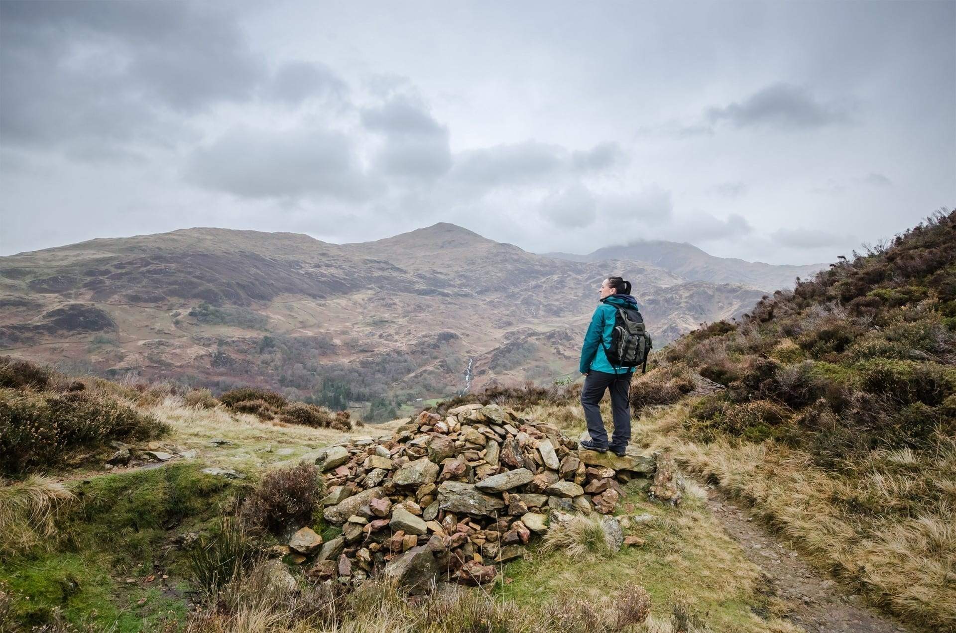 Female hiker with waterproof coat and backpack enjoying the view from the top of a hill in the Snowdonia National Park, Wales, UK