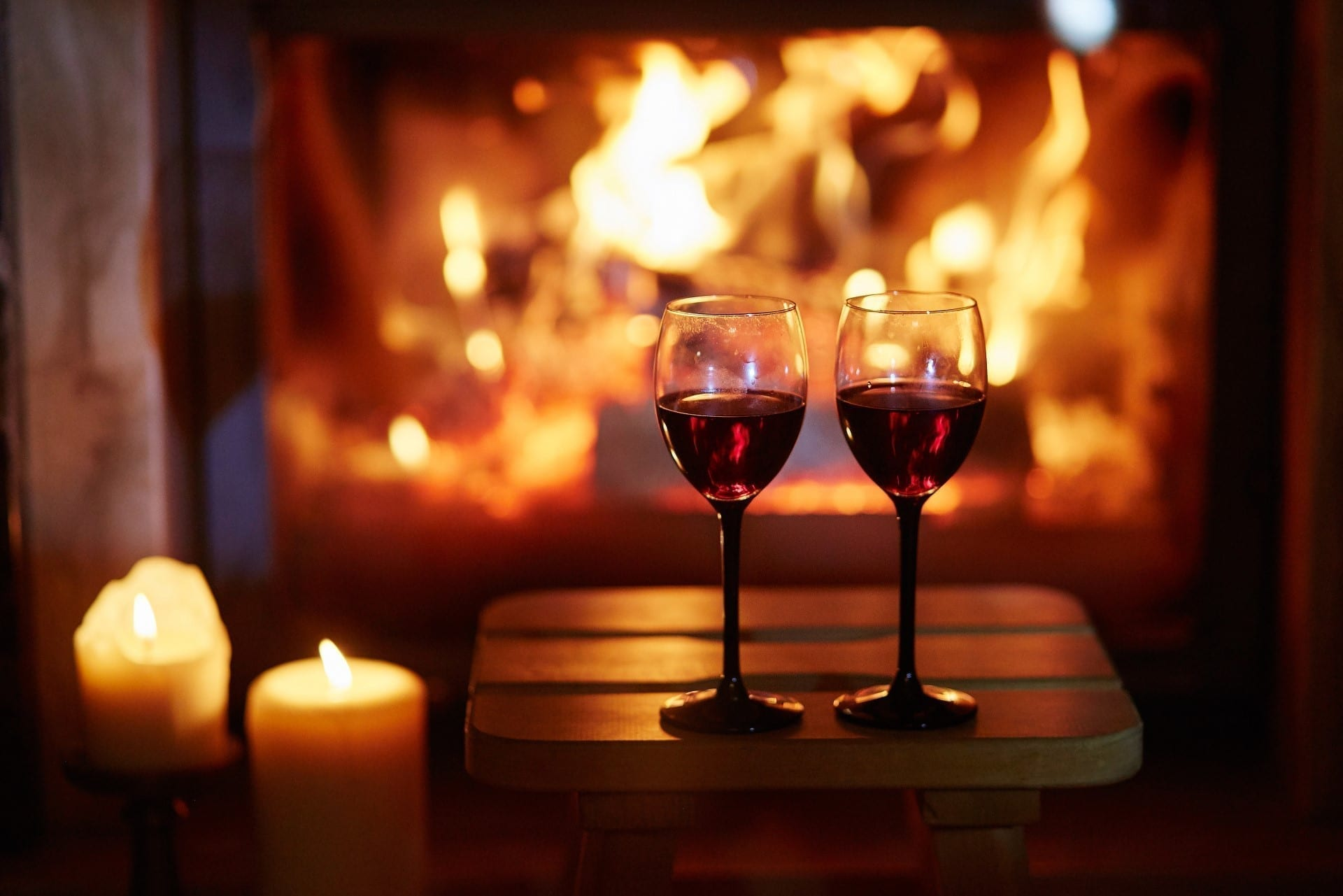 Two glasses of red wine near fireplace with many candles
