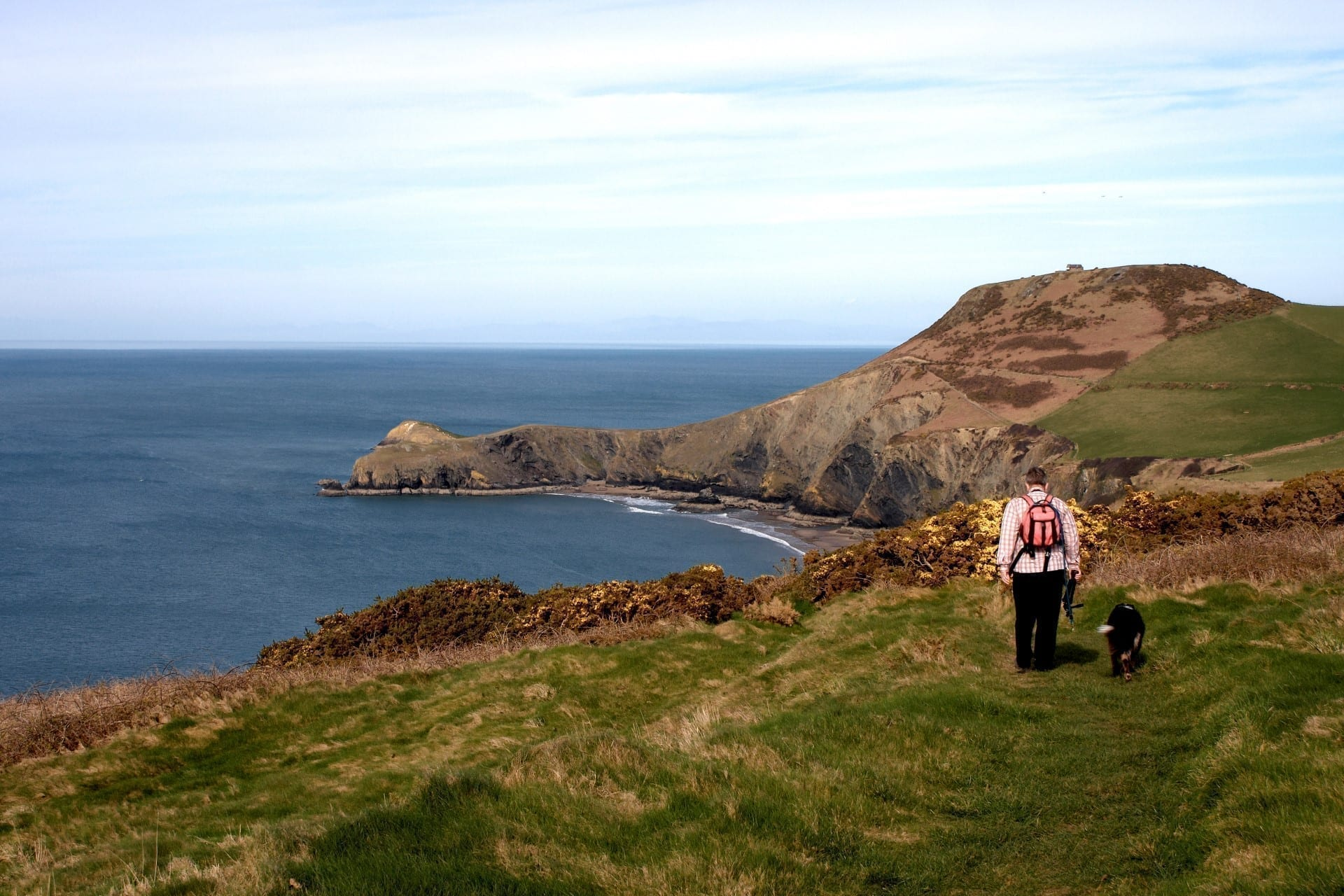 A man and his dog walking along the welsh coastal path